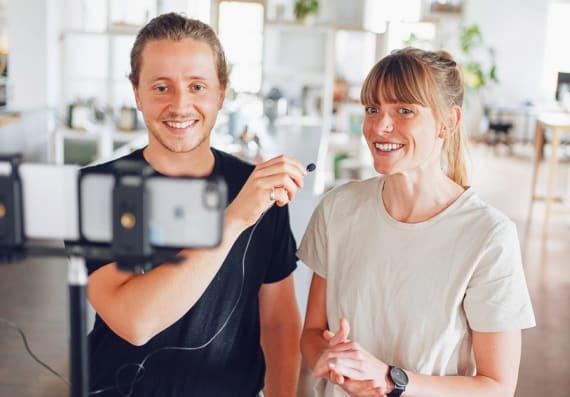 Jannes und Christina stehen vor einer Kamera.