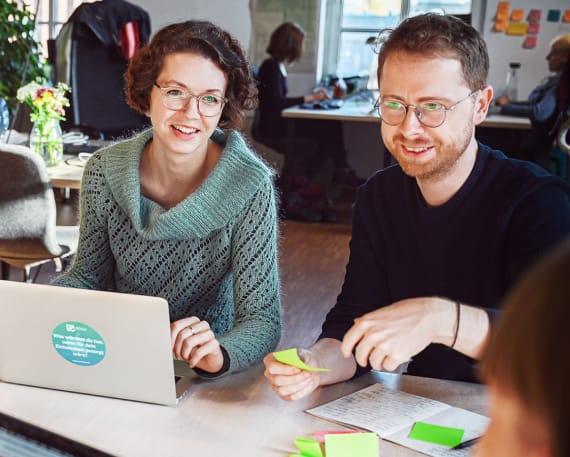 Magdalena und Volker sitzen nebeneinander an einem Konferenztisch in einer Besprechung.