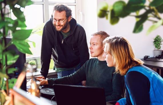 Paul, Pes und Uli sind um einen Bildschirm versammelt und besprechen etwas.